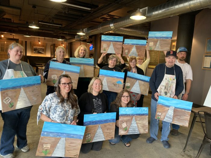 Group shot of all who participated holding their paintings of the Muskegon Pere Maquette Boardwalk