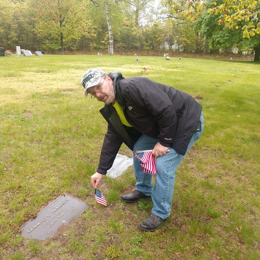 Veteran Howard Fisher placing flag on gravesite